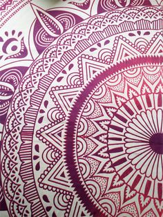 A rectangular mandala tapestry comprising of floral inspired patterns in shades of purples and pinks.