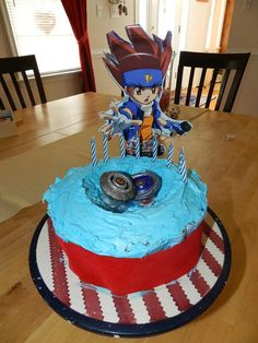 Beyblade cake...homemade! Super easy. Cut out the cent of the cake (bake in a bowl), add beyblades and cut out of the charactor (I used the one from a plate so it would stay up and then taped on toothpicks to stick it into the cake).