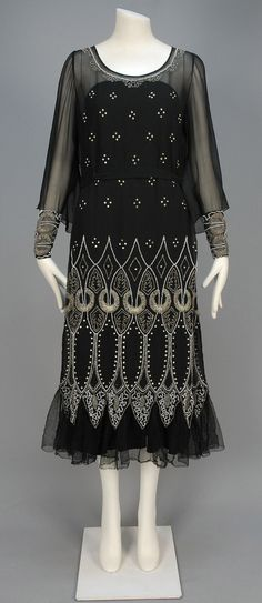 1920s beaded chiffon dinner dress. Black silk Arabesque pattern of crystal and milk glass beads with prong set rhinestones, long flared sleeves with beaded narrow cuffs, Van Dyke pointed hem over tulle ruffle, and self belt.