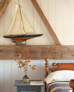 Nautical Touch  A model sailboat is displayed on a beam above an antique American rope bed in a guest room of a barn that was converted into a home.