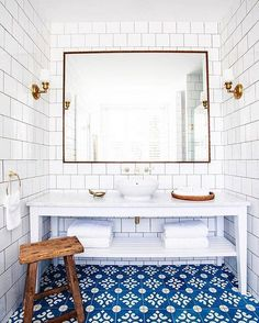 Achieve a bright, clean bathroom with white tile walls and vanity, a printed tile floor, and gold fixtures