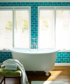 Blue floor to ceiling subway tile and a stand alone tub in a Katie Ridder designed bath. http://cococozy.com
