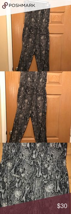 Express romper Express halter romper with draw string waist and snack skin print.  Elastic top flat 14 Waist flat 15' Length 49' Color is tricky. Sometimes it looks a dark green but most times gray No material tag. Feels like a cotton silk blend Express Pants Jumpsuits & Rompers