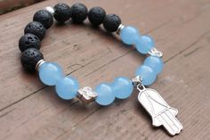 What you see is what you get - this is the only one of this bracelet I will make! Get it before its gone! - 10mm aquamarine genuine round stone beads. - 10mm black lava stone be ads. - Silver tone Hamsa Hand charm and accents. - 7 Inches un-stretched (approximately). This bracelet best fits people with a medium frame. - Ships from Canada.  The stones on this bracelet keep the wearer calm and the Hamsa Hand protects from the evil eye. Lava stone is also a natural oil diffuser! This bracelet…