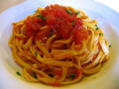 Strangozzi alla spoletina. home-made pasta typical of Spoleto made with flour and water. it is cut up in long strips, then immersed in boiling water for a few moments. it is served with a sauce made with tomato, garlic and chilli.