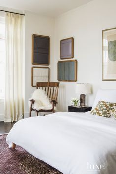 In the master bedroom, pale-hued bedding and Romo drapery fabric provide a subdued backdrop for the Liu Wei oil-on-wood artworks, which intentionally crack and change color over time. The owners commissioned the rocking chair from an artist in Virginia.