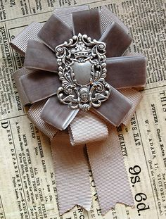 this rosette features a vintage silvertone filigree, surrounded by tiers of grey velvet and petersham grosgrain ribbons.    this rosette measures approximately 4 inches wide and 6 inches tall.    all mossbadger rosettes have a combination back so they can be worn as a brooch or hairclip.