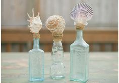 Sea shells in vintage blue bottles with rustic twine is a great centerpiece decor idea for vintage inspired beach or nautical weddings.