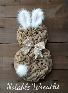 This aborable bunny wreath is made with natural burlap and accented with a faux fur tail and ears and a natural and white polka dot bow. Wreath pictured measures at around 24- 25 L (top of ears to bottom of wreath) by around 14- 15 W.