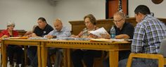 GREGORY RIPPS --  Floresville City Council members Sherry Martinez Castillo (l-r), Mario Morones, and Johnny Ray Nieto, Mayor Diana Garza, and council members John Guerrero and Eric Rodriguez review minutes at the outset of their Oct. 23 meeting, which took place in a courtroom at the Wilson County Sheriff's Office, due to early voting taking place in the council chambers at City Hall.