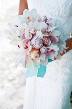 Shells and flowers combine for a beautiful beach wedding bouquet.