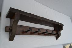 Solid wood shelf with railroad spike hooks. Some distressing. Dark stain.  Has metal brackets on each side to hang from wall.    *****Customized