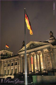 Building of the German Parliament - Deutscher Bundestag with german flag by night - Reichstagsgebäude am Platz der Republik - Berlin Germany/Deutschland