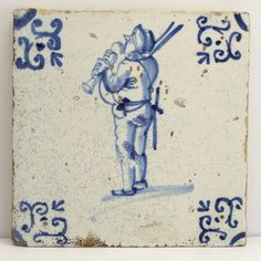 Dutch Delft blue and white tile with bagpipe-player. Period: 1st half 17th century. Large central motif with bagpipe-player. Large ox-head corner motif.