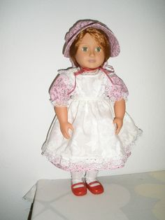 Pink cotton dress, white lacy pinafore, and bonnet.
