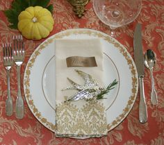 Place setting with gold toned bird and spring of rosemary