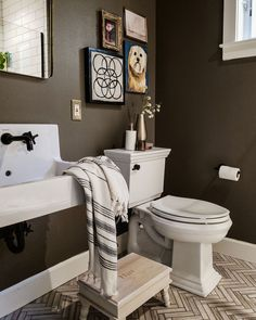 A gallery wall using pieces you already own is one of the easiest budget bathroom decor ideas you'll find. The paint color featured is Dirty Chai by Clare.