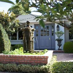 A beautiful gray front door and brick fountain greet visitors at Barclay's Newport Beach home.