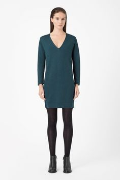 Softly draped at the front, this tunic-style dress is made from finely knitted wool and has a deep v-neckline.  Designed to pull on, it is a loose, relaxed fit with wide 7/8 sleeves and neat ribbed edges.