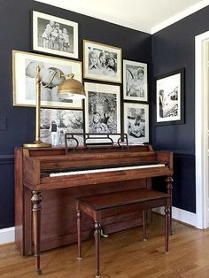 black and white prints on a dark with a brass lamp and the vintage wood of the piano