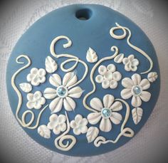 Polymer clay pendant, handmade with applique technique, one of a kind. Light blue with white flowers, leaves and swirls and light blue crystals. By Lis Shteindel.