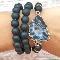 The Isla Bracelet Stack is composed of gorgeous ebony hues. This stack includes 3 separate bracelets with solid ebony sea glass-esque beads and a 14k gold edged black and white agate pendant. Bracelet
