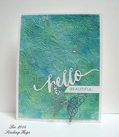 handmade greeting card ... luv the embossing folder flowers with the Gelato inked paper in blues ... brght white HELLO die cut in script font ... shiny silver lacy butterfly ... delightful!