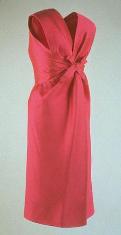 1960. Automne-hiver. Designer: Hubert de Givenchy in France Medium: Silk radzimir Short evening dress in deep pink silk radzimir. (Model number 3118). Minimal detail on front of dress, back has ribbed-weave shot-silk fabric twisted and finished with a hand tied bow. Evening Dress worn by Jacqueline Kennedy to a Staff Christmas reception at the White House December 12, 1962