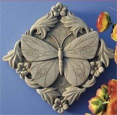 Acanthus Butterfly Plaque Hand Cast Stone (Natural Stone) by Carruth Studio. $38.00. This butterfly surrounded by flowers evokes a sense of peace and a connection with nature. It makes a lovely gift, and is the perfect accent for any garden, deck or sunroom. It is slightly larger than most plaques, and can be displayed hanging or resting in a flower bed or lawn.