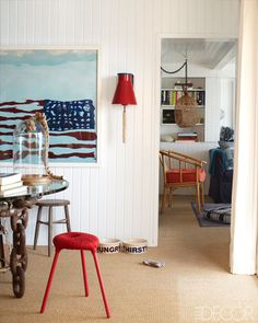 A photograph by Oberto Gili hangs next to a vintage ship's bell in the dining room