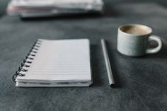 FREE STOCK PHOTO: Coseup of blank empty notepad, pencil and cup of coffee on grey desk
