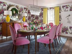 Pink fabric on dining room chairs and a splashy Clarke & Clarke wallpaper with a nostalgic feel drench the dining room in color. - Photo: Nancy Nolan / Design: Tobi Fairley