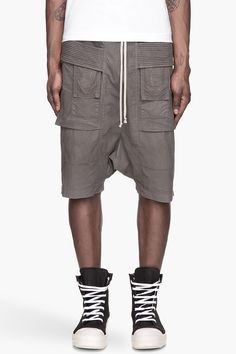 Rick Owens Drkshdw Dark Grey Banded Poplin Cargo Shorts -  Rick Owens Drkshdw Dark Grey Banded Poplin Cargo Shorts Rick Owens Drkshdw Loose_fit low_rise draping cargo shorts in dark grey. Six_pocket styling. Corded accent bands at sides. Elasticized waistband with drawstring. Tonal stitching. Price $620.00