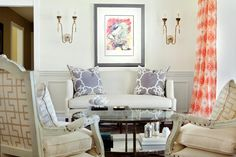 Beautiful living room with grey wainscoting features abstract art flanked by gold French candle wall sconces above an ivory sofa topped with grey accent pillows facing a glass top oval coffee table beside a pair of whitewashed French chairs. Wainscoting Height, Wainscoting Nursery, Dining Room Wainscoting, Wainscoting Styles, Wainscoting Panels, Black Wainscoting, Painted Wainscoting, Sconces Living Room, Living Room Grey