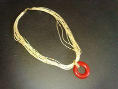 Fios beges, com pequenas contas douradas e o pingente contrastante em resina tipo pedra sabão em vermelho.