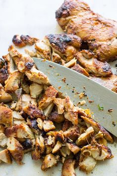 Chipotle Chicken - a photo of cooked chipotle chicken diced into smaller pieces with a silver knife on a white background - click photo for full written recipe