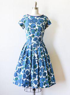 Schattig vintage 50s blauwe bloemen jurk. Wit met grote blauw en groen steeg bloemenprint, met paarse bekleding rond de kraag. Korte mouwen, ingerichte taille met riem loops en volledige rok. Metalen rits op de rug met haak sluiting. Bekleed. Er is een paar kleine bleekmiddel vlekken onder de linkerarm, samen met sommige onderarm pilling aan elke kant. De rits heeft een beetje van de schrijnende het weefsel in de buurt van de taille, maar dit heeft geen invloed op de slijtage, zie fotos…