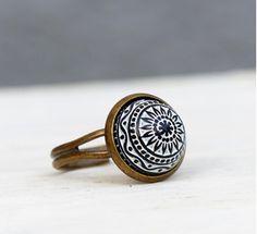 Bronzefarbener Ring mit einem marokkanischen Relief.  Der Knopfstein ist weiß und das Relief ist schwarz eingefärbt, daher ist  der Ring besonders interessant und wirkt als wäre er direkt in  Marrakesch...