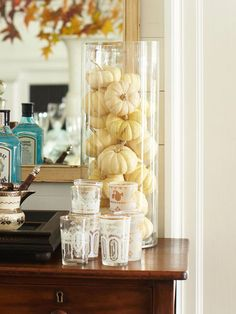 Even the simplest of objects, when displayed on a larger scale, can have a stunning affect. Here, a tall cylindrical vase is filled to the top with basic white pumpkins and is perched atop a dining room buffet for an eye-catching display.