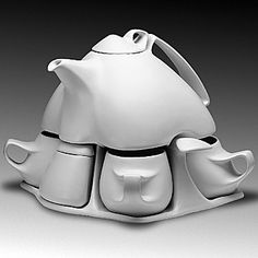 """Work by Peter Saenger in the gift store of the American Museum of Ceramic Art. Service for Four (porcelain,white glaze) eleven-piece set: pot (60oz), lid, four mugs (8oz), sugar bowl with lid, creamer, warming candle, tray 12""""x10""""x9"""""""