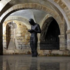 The sculpture by Antony Gormley that appears in Winchester Cathedral contemplates the water.