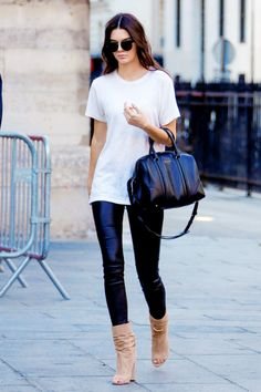 Kendall Jenner is killing it in a white tee shirt, leather pants, nude heels, and a black bag.