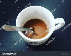 Semi-empty white coffee mug. Spoon in coffee.