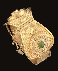 """A MOROCCAN GEMSET GOLD BRACELET (KHLKHLA)   FEZ, EARLY 20TH CENTURY   The gold flat band hinged in the centre and expanding into two large lobed panels near the pin clasp, the surface very finely carved with scrolling motifs, the large panels each with a prominent raised circular panel set with a band of rose-cut diamonds around a cabochon emerald, the settings bright-cut, the shanks each with a small inset ruby, the pin attached by chains with heart and """"hand of Fatima"""" pendants"""