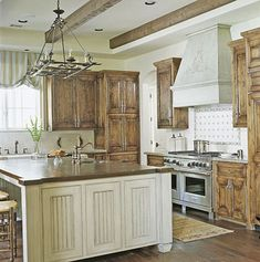 """Old World appeal """"Light walls serve as a quiet backdrop for strong architectural elements, pine cabinets, and an island with a 2-inch-thick mahogany top. These elements, along with the cabinetry's distressed finish and the dark warmth of the beveled walnut wood floors, combine to create an old French feel, which blends with the rest of the home."""""""