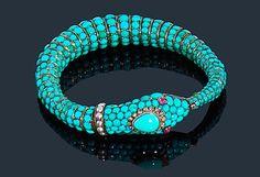 Bracelet serpent en or 14K (585‰), le corps entièrement serti de turquoises cabochons, la tête surmontée de diamants taillés en roses, les yeux en rubis cabochons, le collier agrémenté de demi-perles (non testées). Travail du XIXe siècle. Longueur : 22,5 cm environ. Poids brut : 52 g