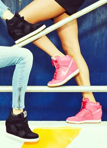 girls wearing high top sneakers | Close-up on the legs of two models wearing high-top wedge sneakers.