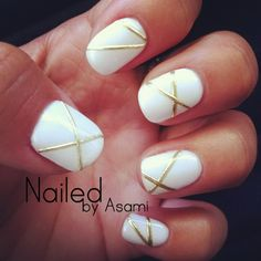 Minimalist white and gold nail art design. The nails have white polish in the background and thin strips of metallic gold on top forming an x pattern.