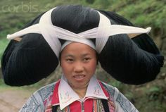 China   A woman from the Long Horn Miao tribe wears a ceremonial hairpiece, woven from her ancestors' hair, over wooden horns. The name of the tribe comes from the wooden horns worn by women to represent the strength of an ox.  Guizhou Province   © Keren Su