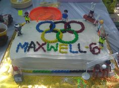 Olympic rings rainbow birthday cake with M and Playmobil Olympians!